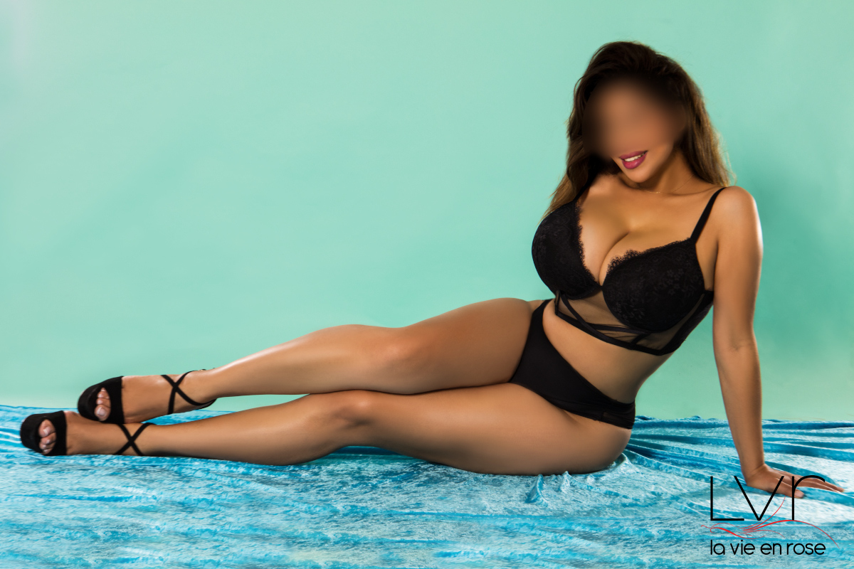 Busty escort in Barcelona on a blue background, Laura