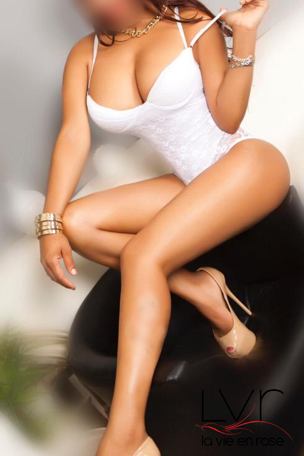 Latina escort with big breasts in Barcelona with a white body in a black armchair, Estrella