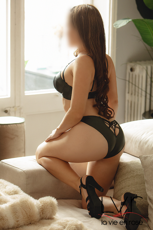 Luxury escort in Barcelona with black lingerie on a sofa, Tatiana