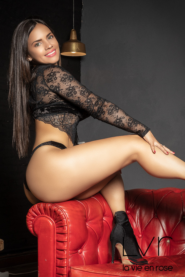 Luxury escort for GFE in Barcelona sitting on a red sofa, Nikol