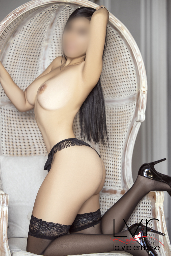 Young Latin escort in Barcelona with black stockings on a chair, Mia