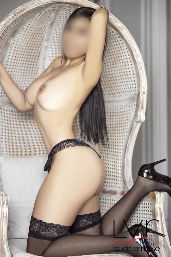 Jeune escorte latine à Barcelone avec des bas noirs sur une chaise, Mia