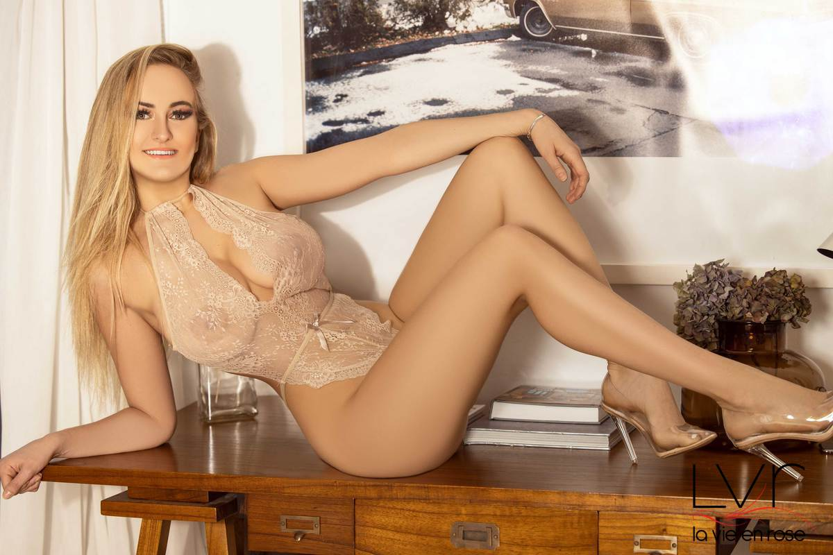 French blonde escort in Barcelona lying on a table with a transparent top, Blondy