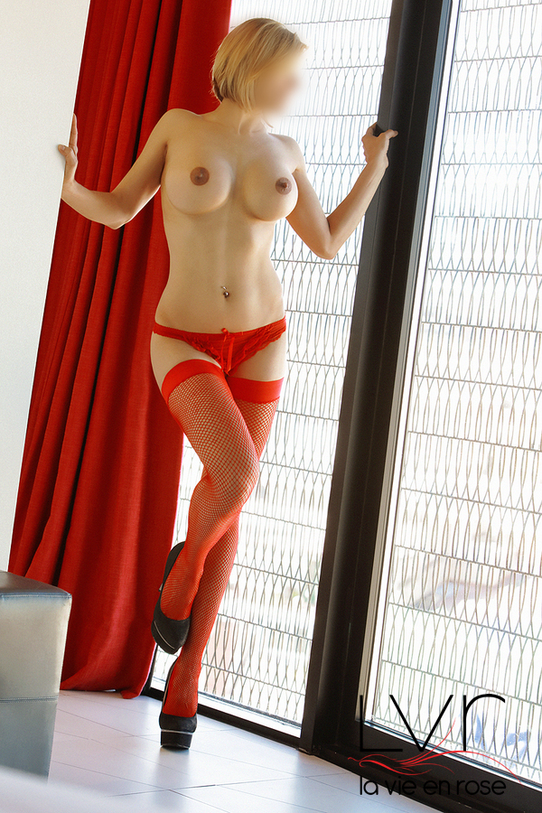 Blonde latina escort in Barcelona with red stockings, María